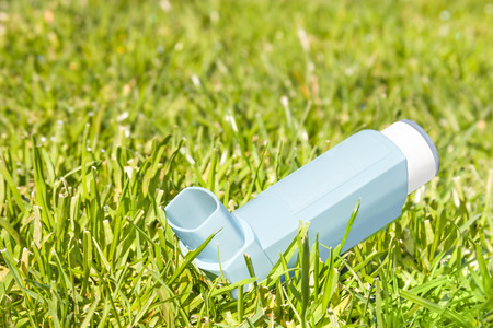 Asthma allergy inhaler sprayer in blades of green grass   Open, plastic inhaler  Low angle view  Breathing fresh air in nature concept  Horizontal photo   photo