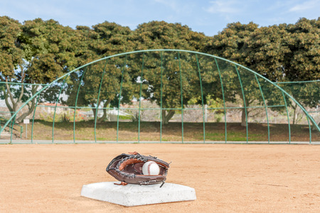 backstop: Baseball glove and ball on second base in red sandy dirt facing backstop   Ball inside mitt  Low angle view from behind base  Trees, blue sky in blurred Horizontal photo