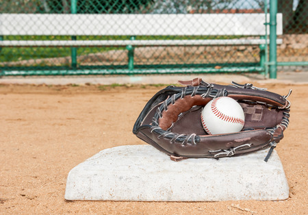 Baseball mitt and ball at first base   Ball inside mitt  Low angle view  Metal player bench and chain link fence in blurred Horizontal view  photo