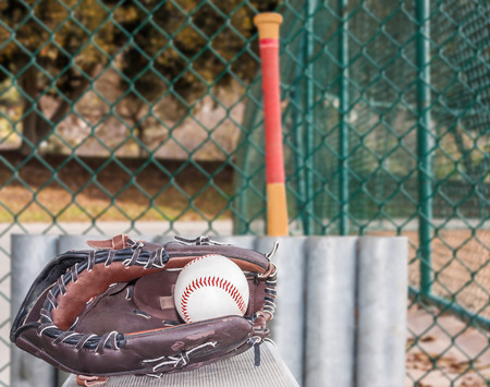 Baseball and glove resting on metal bench in dugout   Ball inside mitt  Low angle view  Baseball bat and storage rack, chain link fence in blurred Horizontal view  photo