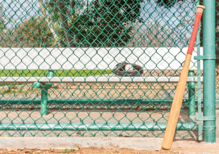 dugout: Wood baseball bat leaning on the dugout chain link fence   Red bat grip tape on the wooden handle  Selective focus on the worn bat  Metal player bench, ball and mitt, trees in the blurry
