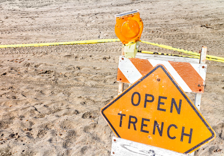 Construction site barrier, open trench warning sign in sand close u photo