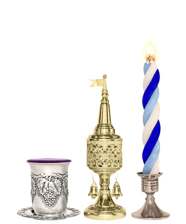 Havdalah set  Silver wine cup, gold color spice box, braided blue and white lit candle, copyspace, vertical view  photo