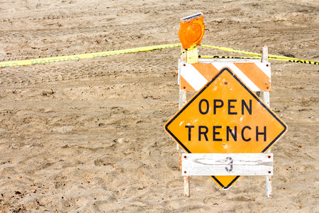 open trench: Construction site barrier, open trench warning sign in sand Stock Photo