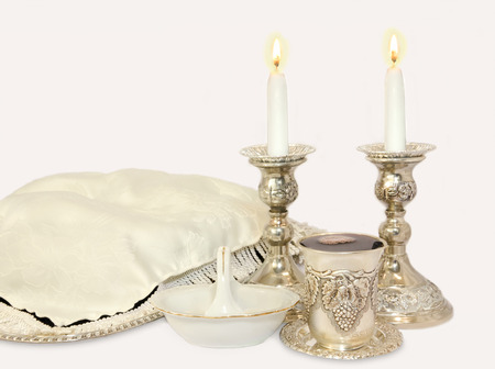 Challah on silver tray covered with fringed white cloth, two glowing wax candles in antique silver candlesticks, decorative kiddush cup with red wine, white porcelain bowl with salt photo
