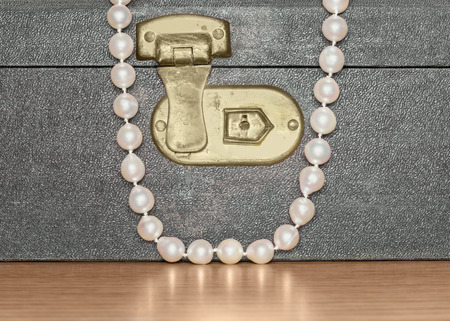 luster: Elegant pearl necklace draped over old, worn vintage jewelry box on wood grain surface, close up   Container is closed and locked, faux leather textured surface  Smooth pearly luster reflection  Horizontal photo   Stock Photo