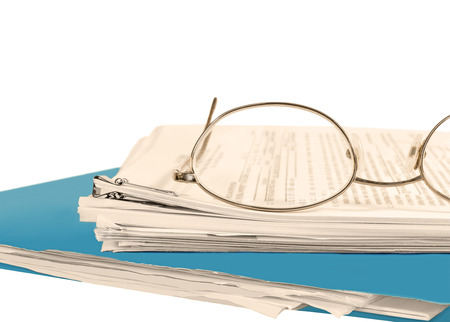 Close up of reading glasses on stack of papers held together with bulldog paper clip  Blue folder on bottom    Blurred text  Horizontal, isolated with room for text, copy space  Office job stress concept  Sepia tint  photo