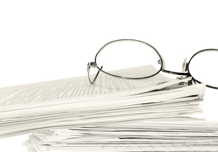 Reading glasses on stack of papers held together with bulldog paper clip   Blurred text  Horizontal, isolated with room for text, copy space  Office job stress concept  Sepia tint  photo