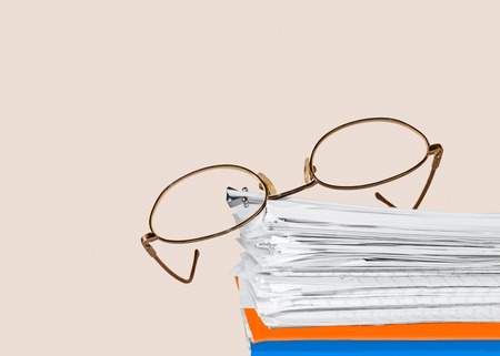 Reading glasses on stack of papers held together with bulldog paper clip  Blue, orange folders on bottom    Horizontal, isolated with room for text, copy space  Office job stress concept   photo