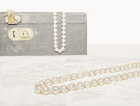Elegant pearl necklace and vintage jewelry box on floral pattern beige cloth   Smooth pearly luster  Closed, unlocked container in isolated blurred background  Horizontal photo   photo