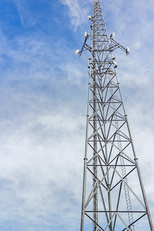Tall steel cellphone tower, perspective view    Steel structure soaring into the blue sky with clouds  Successful wireless network communication concept  Vertical photo  photo