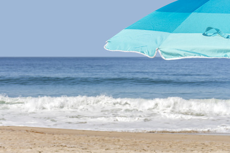 Blue beach umbrella by the ocean  photo