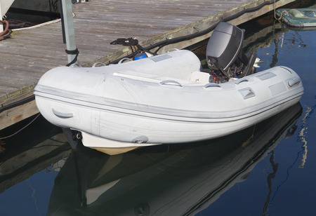 Recreational inflatable white rubber raft with outboard motor tied to wooden dock   Reflection of dinghy in the still water  Horizontal marine scene  photo