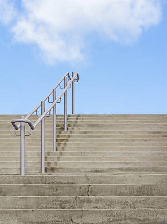 Outdoor stone stairs and blue sky with clouds   Rough texture steps with metal handrail going up  Vertical photo   photo