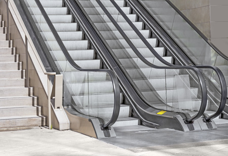 Pair of outdoor modern escalators next to a stone stairway, stone tile floor   Gray metal textured steps, black handrail  Clear acrylic or plastic sides