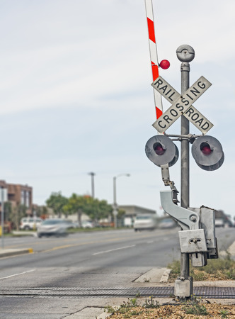 Railroad crossing sign on urban street with traffic   Shows red and white striped gate arm, signal lights, part of train tracks    photo