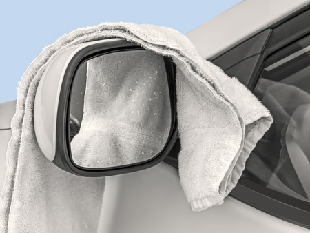 drying: Soft white towel and wet car side mirror close up   Water drops on glass  Blue background   Stock Photo