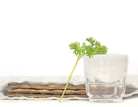 Passover fresh green parsley, saltwater, and matzah    Part of the seder ritual is dipping parsley, known in Hebrew as karpas, in saltwater  Focus on leaves, clear glass cup  3 covered matzahs blurred in background  Isolated on white  photo