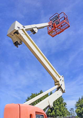 reach truck: Cherry picker or boom lift reaching high up    Red elevated work bucket platform, articulating bending arm mounted on an orange truck  Trees