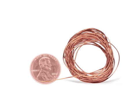 conducting: Thin bright copper electrical wire with faded and blurred Lincoln penny   Concept of less raw copper material in coins  Wire wound in a circle shape with strand extending outward  Drop shadow  Room for text, copy space