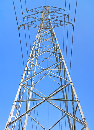One high voltage electrical power transmission line tower, front low angle perspective view   Steel lattice pylon structure, wires, insulator capacitors  Sharp pointed spikes on legs and diagonal bars as climbing deterrent  Blue sky  photo