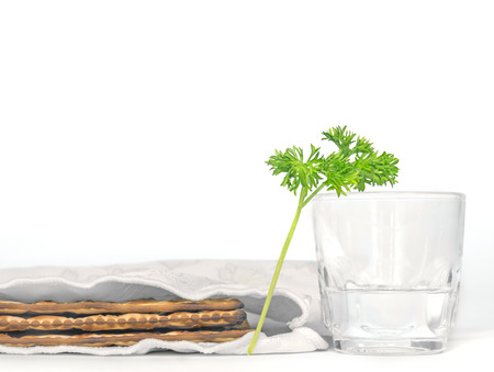 Passover holiday fresh green parsley, saltwater in clear glass cup, matzah   Part of the seder ritual is dipping parsley, known in Hebrew as karpas, in saltwater   Shown with 3 covered matzahs  Isolated on a white background  photo