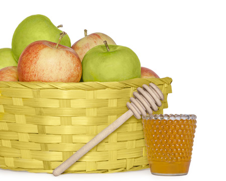 Basket of apples for Rosh Hashana apples, glass jar of golden honey, and wood stick symbols of the Jewish New Year   photo