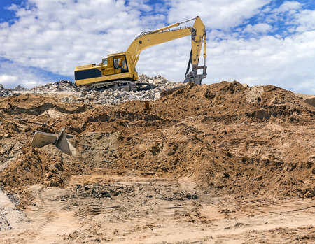 machinery: Heavy construction yellow excavator vehicle at demolition site   Broken concrete, rocks, and soil  Cloudy blue sky background  Horizontal composition    Stock Photo