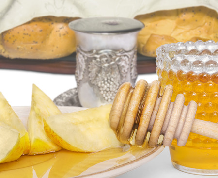 Flowing honey and apple slices for Rosh Hashana, the Jewish New Year   Glass honey jar, wood stick dripping sweet honey, cut apple wedges on plate  Covered challah bread loaves, silver kiddush cup filled with wine in background  Close up, macro view  photo
