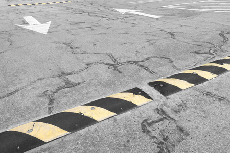 Traffic safety yellow and black speed bump in empty parking lot    Road markings of two way white arrows pointing opposite directions in background  Dirty cracked asphalt  Horizontal photo  photo