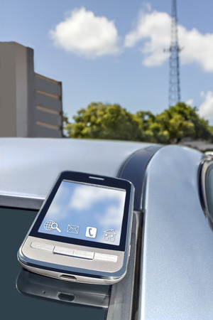 telecommunication tower: Cell phone on top of car roof rear window, telecommunication tower and building   Urban wireless reception concept  Blue sky and clouds background  Vertical photo