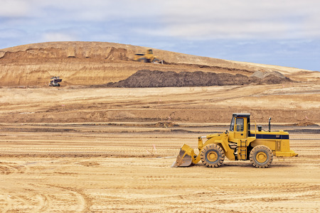 Heavy construction loader vehicle at worksite   Wide open space of sandy dirt  Hill, overcast sky and clouds in background  photo