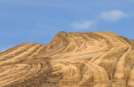 dirt: Construction dirt pile   Large hill of sandy soil with vehicle tire tracks on the surface  Blue sky and clouds background