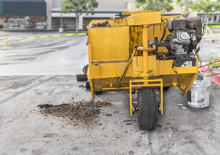 grader: Front of paver grader road resurfacing vehicle parked in suburban empty parking lot showing machine ohv engine and tire    Yellow caution ribbon, wet tar on pavement, commercial building in background