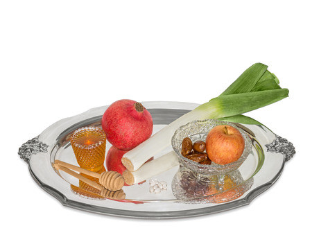 jewish cuisine: Traditional Rosh Hashana sweet food for the Jewish New Year   Sephardic style holiday cuisine  Apple, honey, pomegranate, leek, and dried dates  Fruit and vegetable reflection on shiny silver tray  Slight drop shadow  Isolated on white background