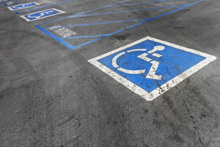 disabled parking sign: Empty handicapped parking spaces with blue and white disabled icon    Black asphalt parking lot  Rough textured surface with tire marks and oil stains  Reserved parking  Blue striped lines, no parking area  Words and pictorial information  Stock Photo