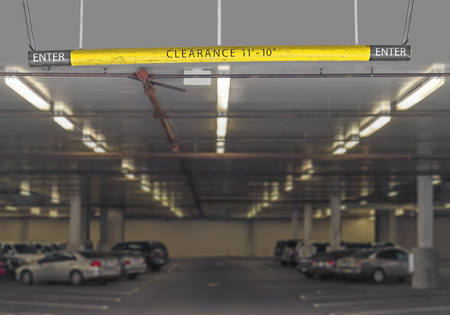 parking lot interior: Indoor parking garage entrance hanging sign with height clearance information   Focus on yellow and black metal beam with words  Fluorescent lighting  Rows of cars and parking spaces in concrete structure  Perspective view  Blurry background