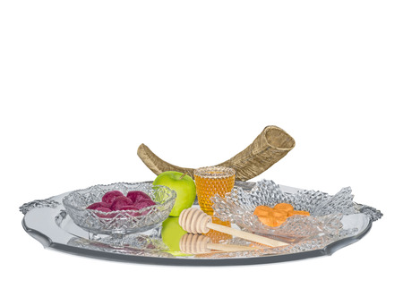 jewish cuisine: Shofar and traditional Rosh Hashana sweet food for the Jewish New Year   Sephardic style cuisine for the holiday  Green apple, honey, beets, carrots  Elegant glass bowls  Reflection on shiny silver tray  Isolated on white background