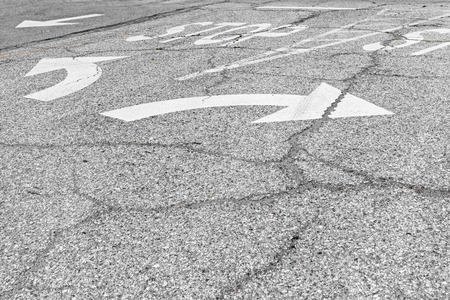rough road: White painted arrow symbol urban road markings in opposite directions for left or right turn   Making a decison concept  Rough texture cracked asphalt surface with the word  stop  in large letters