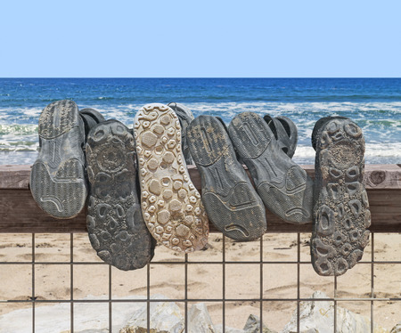 Sandy shoe and sandal soles hanging over a wood and metal wire fence on the beach   Walking on the beach concept  Sand in shoe tread  Blue ocean water waves, sky, horizon in background  photo