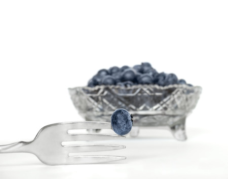 tine: Single fresh blueberry stuck on the point of a metal fork tine close up   Silver color eating utensil  Clear glass bowl of blueberries in blurred background  Isolated on white  Stock Photo
