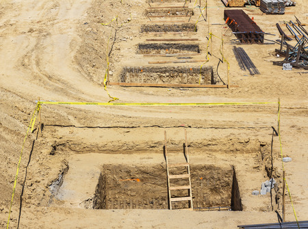 open trench: Wood ladder in construction site excavation hole   Preparing the foundation of a new development with group of rectangular trenches  Pile of steel rebar and concrete blocks in the sandy soil