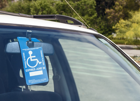 Disabled person parking blue and white permit placard   Wheelchair icon, instructions, and expiration date  Hanging from car rear view mirror, visible through front windshield in rural parking lot  photo