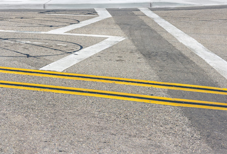 Double yellow lines and roadway vehicle detection loop sensors   Painted road marking lines and circular inductive detectors embedded in asphalt   photo