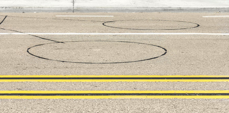 Roadway vehicle detection loop sensors and road markings   Circular inductive detectors embedded in asphalt  Two sets of double yellow lines dividing the street  photo