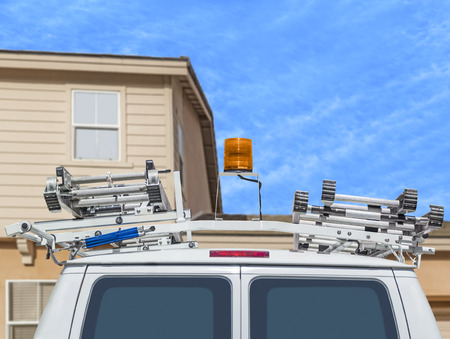 Home repair contractor van back view   Utility truck with metal ladders parked in front of house  Orange emergency warning light on vehicle roof  photo
