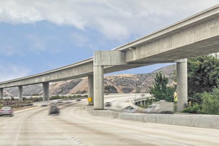 Rural highway overhead interchange structure   Curved concrete overpass above fast moving cars  Blue sky and clouds background  Blurred motion  photo
