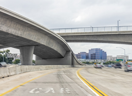 roadway: Urban highway concrete overpass structure and pedestrian bridge walkway viewed from the carpool lane   Fast moving cars, blurred motion  Background city buildings  Cloudy overcast sky