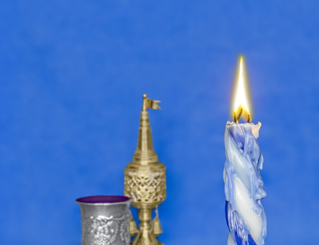 sabbath: Havdalah set, braided lit candle dripping wax    Jewish religious ritual objects used for conclusion of Sabbath