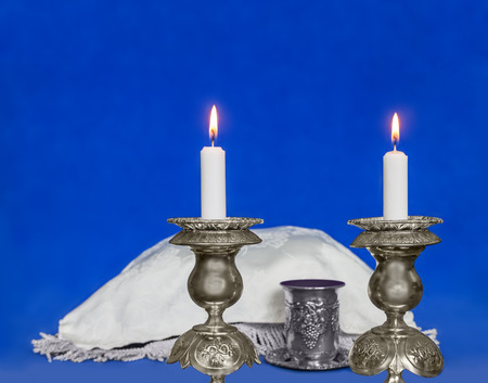 Glowing Sabbath candles on blurred blue soft texture background.  Selective focus closeup on two wax candles in antique silver candlesticks  Covered challah and kiddush cup with red wine in background  photo